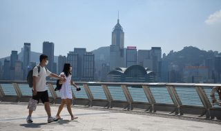 A-couple-walk-on-Avenue-of-Stars-with-the-Hong-Kong-island-skyline-on-the-background
