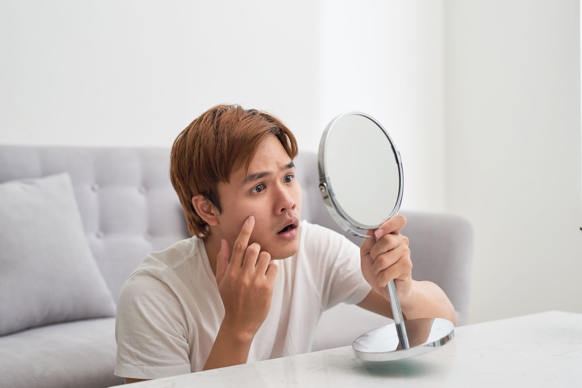 asian-man-looking-at-his-acne