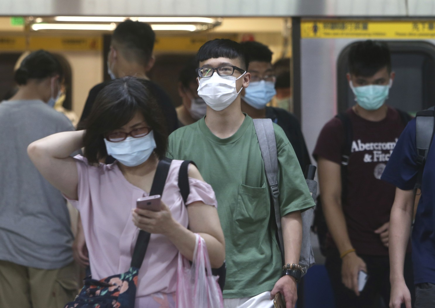 asians wearing masks at a train station