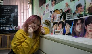 Ms Ng Kwok Ching poses with the BTS portraits she drew and her Loveholic Beauty cosmetics