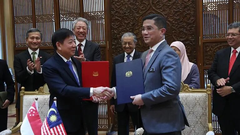 Singapore Transport Minister Khaw Boon Wan (left) and Malaysian Economic Affairs Minister Azmin Ali exchange documents in Putrajaya on Sep 5, 2018