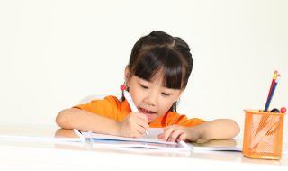 an asian child writing on a desk