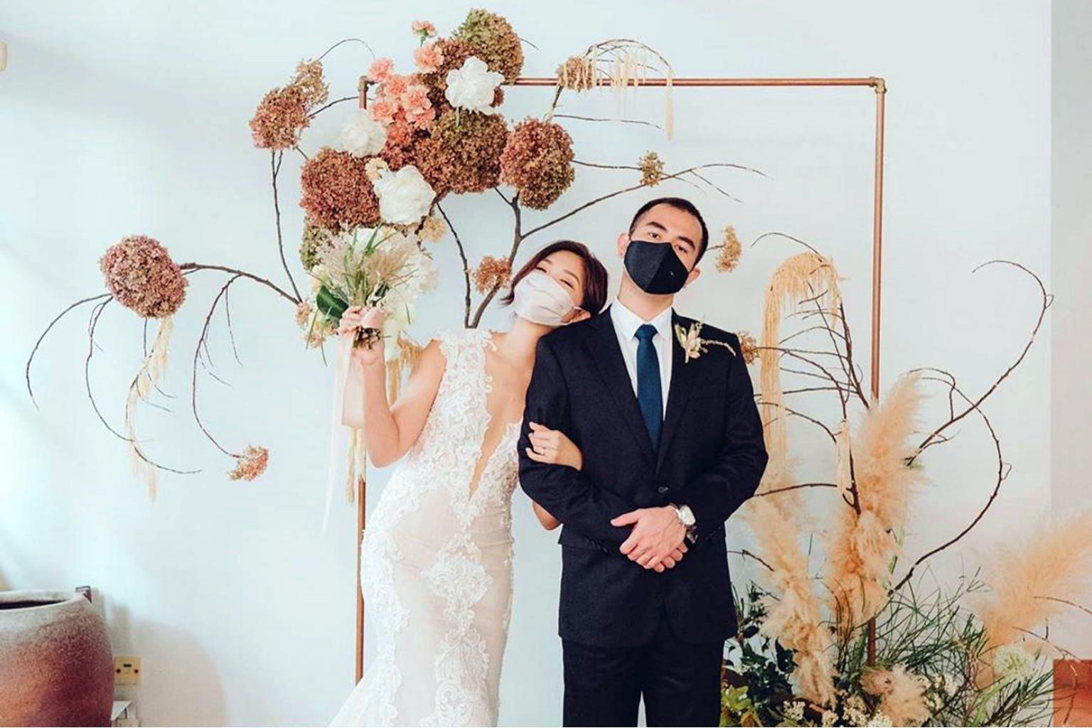a couple wearing masks for a wedding photo