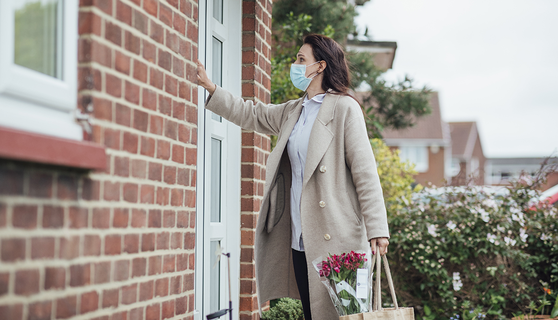 a lady with a face mask knocking on the door