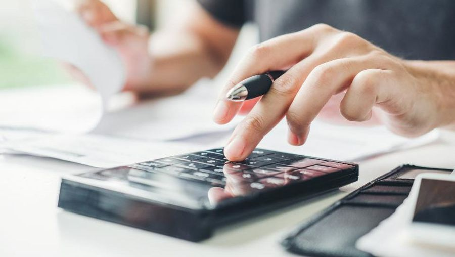 a person calculating while budgeting