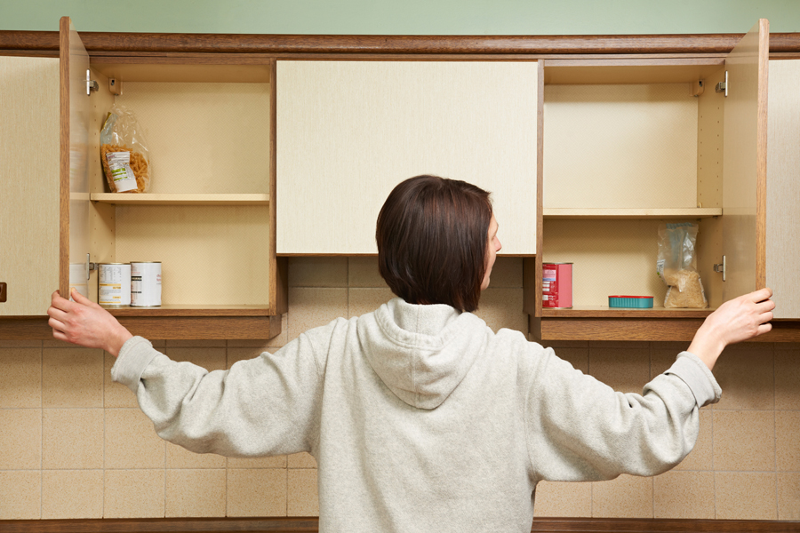 a woman standing in front of a kitchen cupboard
