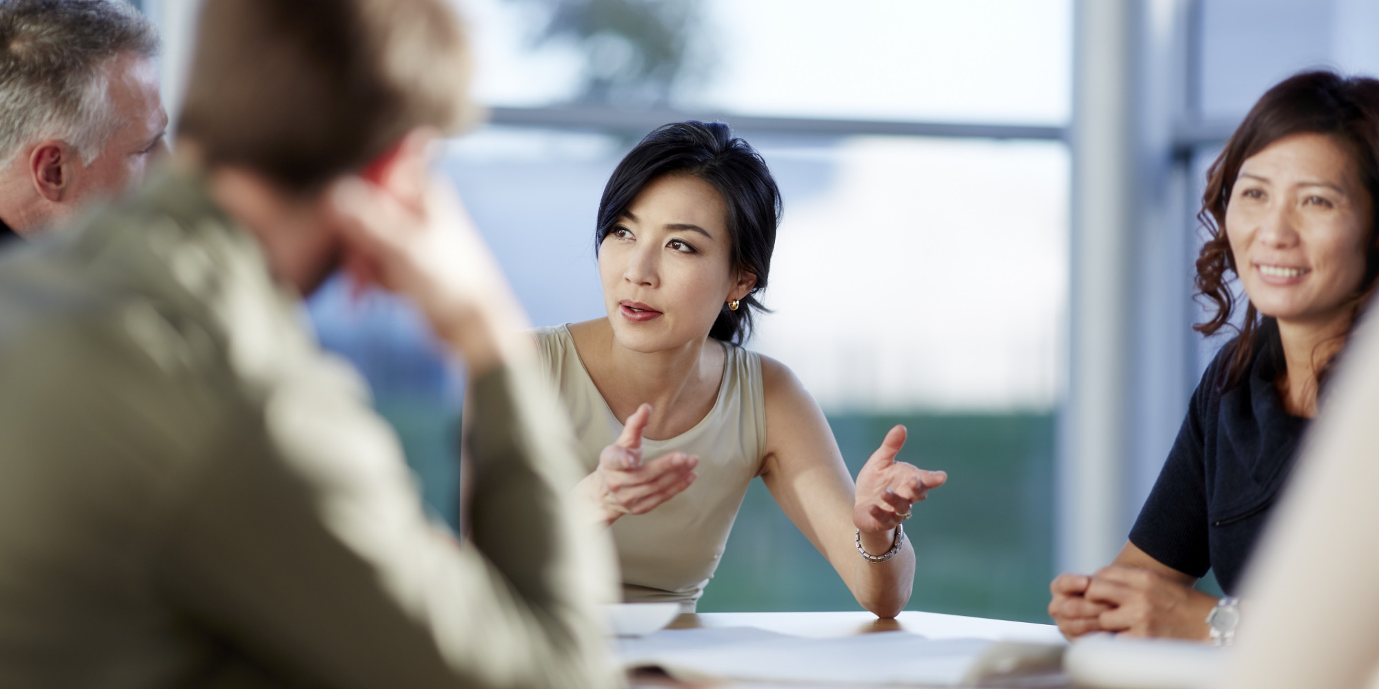 an asian woman asking questions at a business meeting