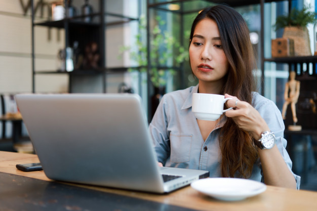asian woman drinking coffee while working in a cafe