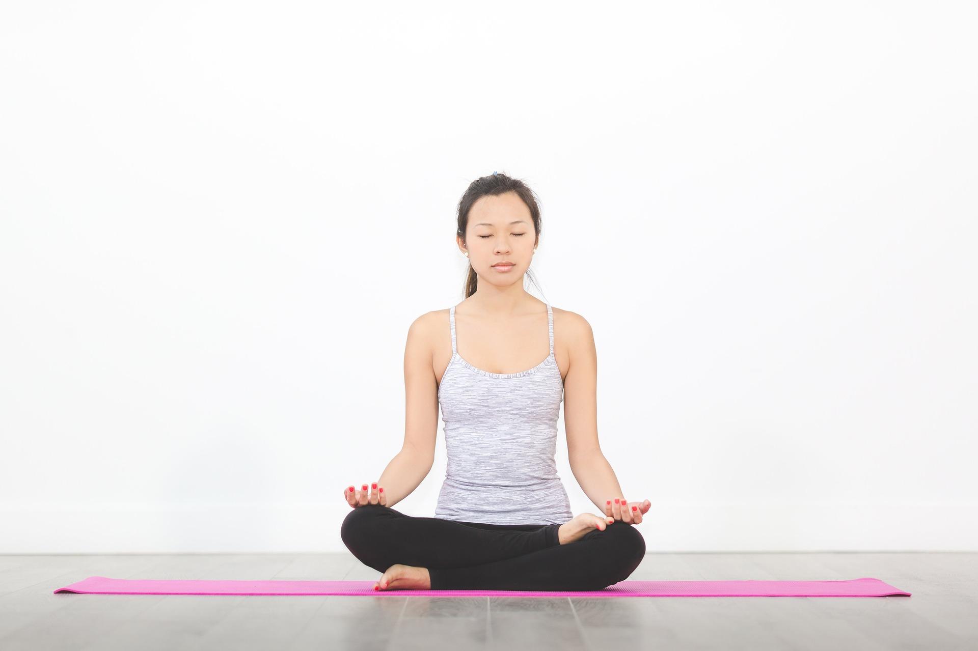 an asian woman meditating on a yoga mat