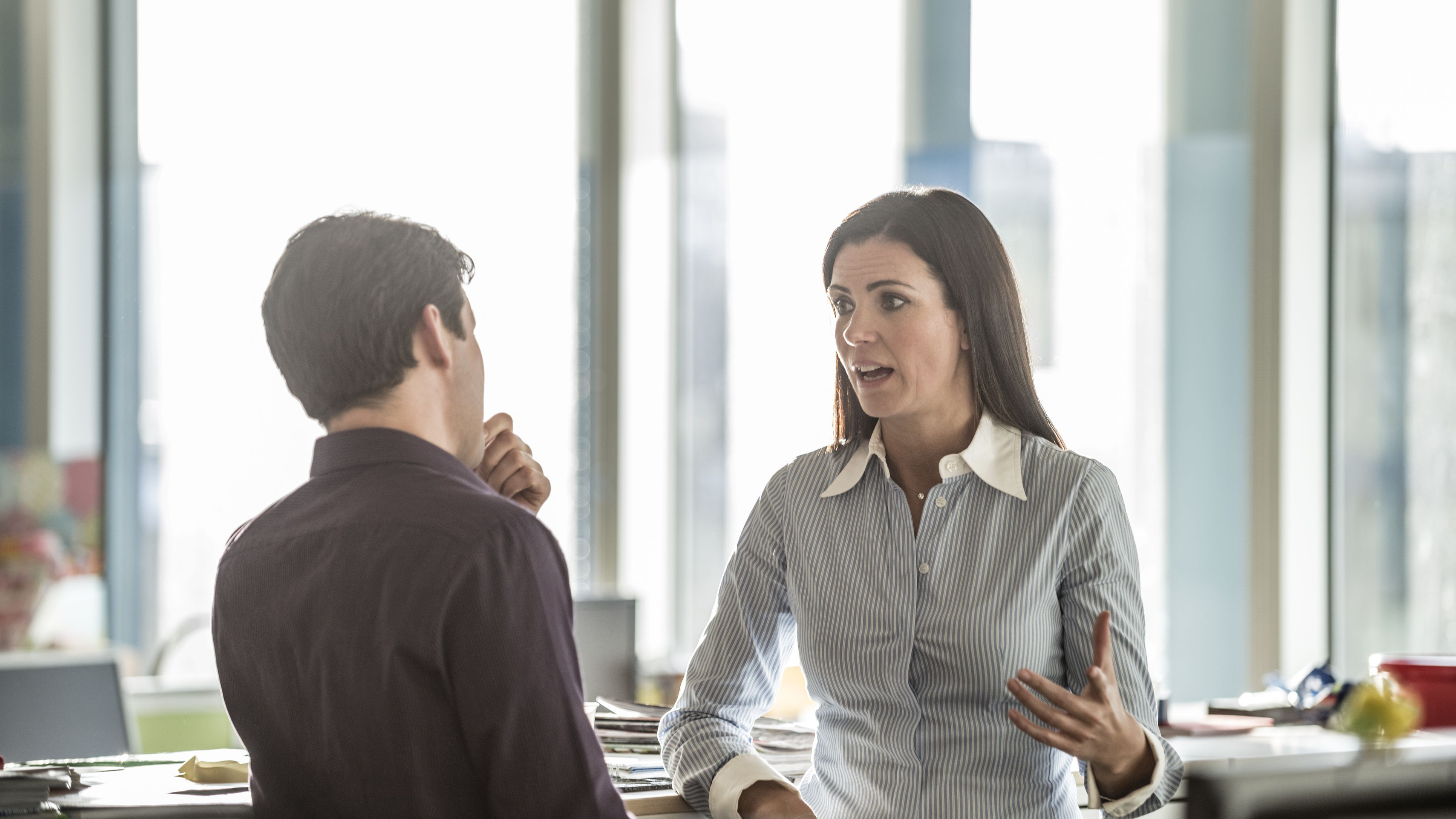 two-business-people-having-serious-discussion-in-the-office