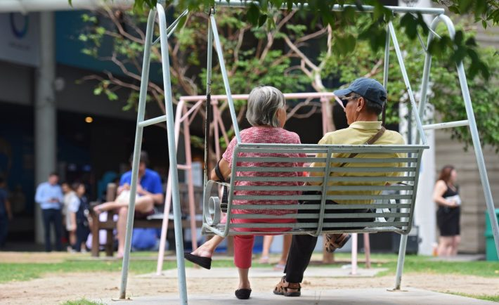 two elderly persons sitting on a swing