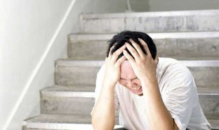 a stressed asian man sitting by the staircase