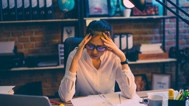 a stressed woman sitting in front of her desk