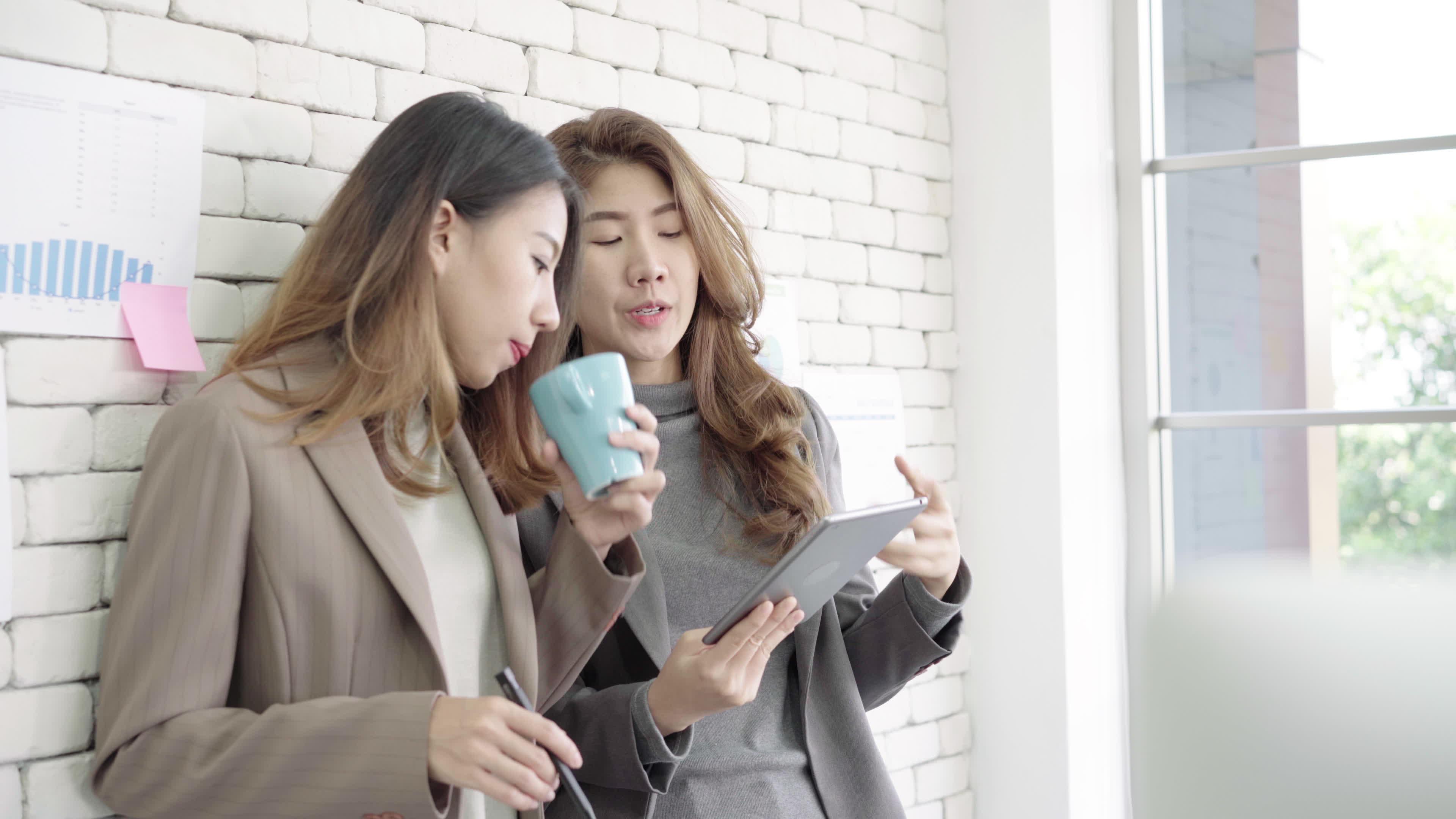 two asian woman talking