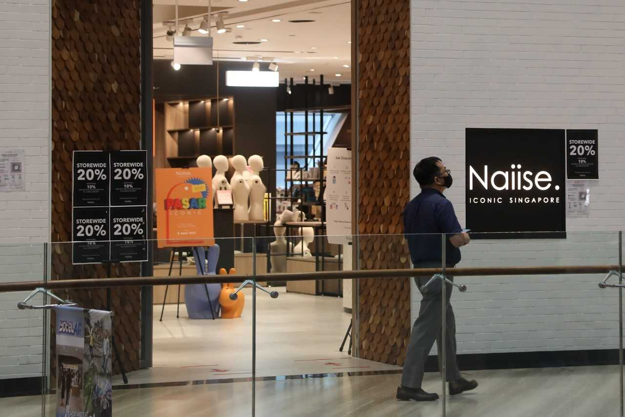 a man walking past the deserted Naiise outlet at Jewel