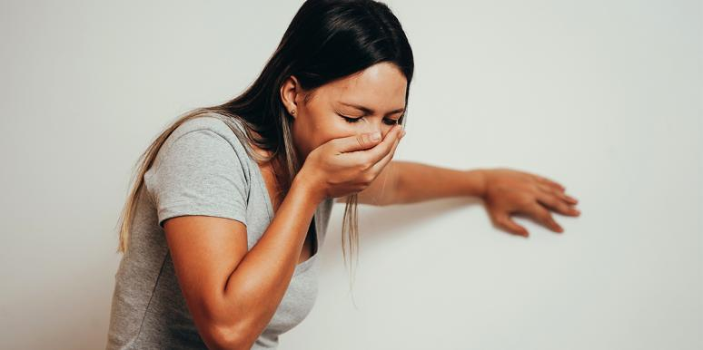 a woman covering her mouth almost vomiting