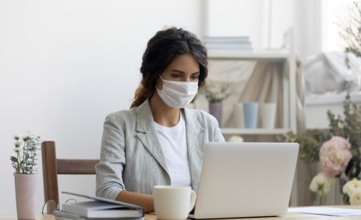 a woman with a face mask working on her laptop