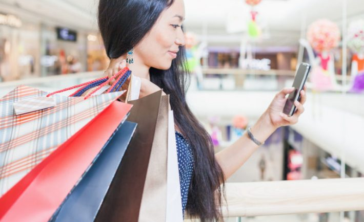 an asian woman carrying shopping bags and looking at her phone