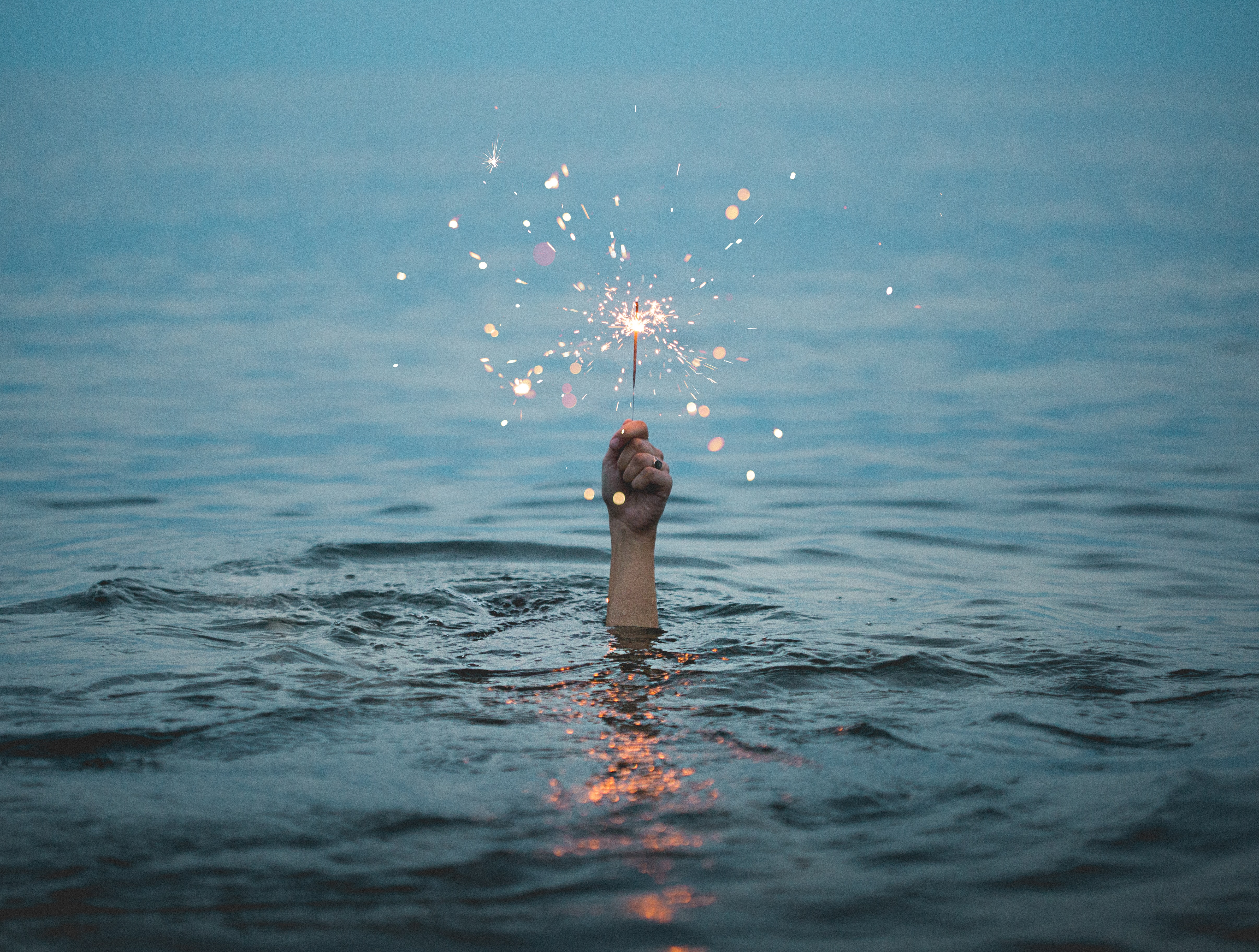 a hand holding a sparkle in the midst of the ocean