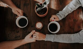 a couple drinking coffee and holding hands