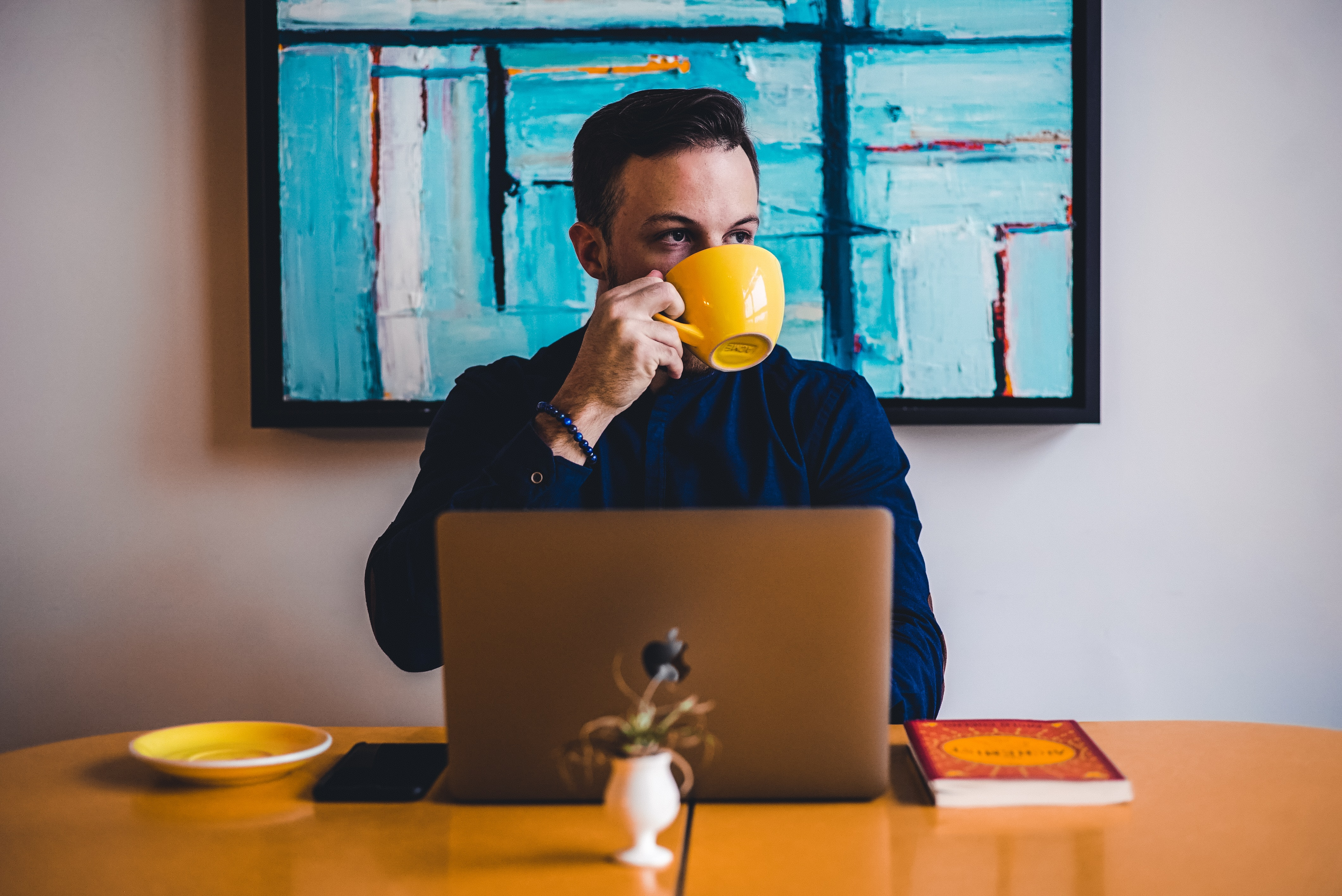 a man drinking coffee in front of his laptop