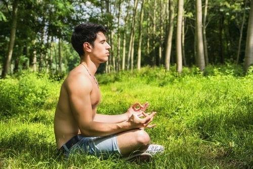 a shirtless man meditating