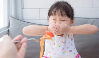 a fussy Asian child at mealtime